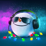 Funny snowball. In the headphones. Christmas party. Musical Background Royalty Free Stock Images