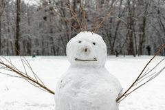Funny snowman with branches instead of hands. Sculpture of snow. Strange and terrifying snowman. Playing outdoors in winter. Family winter fun in the forest stock photo