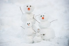 Funny snowman family on the snow Stock Photos