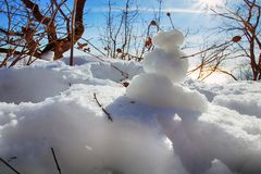 Funny snowman in rays of sun. Funny Frosty (snowman) in forest in rays of sun, against light. Winter fun, make snow. Figures of snow for children and youth royalty free stock image