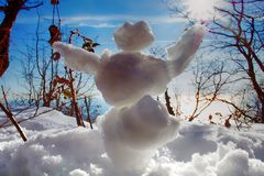 Funny snowman in rays of sun. Funny Frosty (snowman) in forest in rays of sun, against light. Winter fun, make snow. Small figures from snow for children and stock image