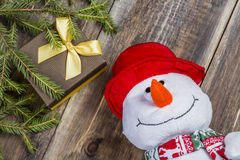 Funny snowman in red hat with gift box and spruce branch on nice wooden background. Royalty Free Stock Photo