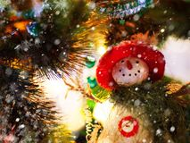 Funny snowman in a red hat and green scarf on the background of Christmas tree branches with lights royalty free stock images