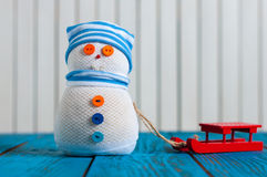 Funny snowman with red sleg or sleigh on wooden Stock Photos