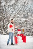 Funny snowman with shopping bag - discount and winter sale concept. Happy smiling snow man on sunny winter day with stock photography