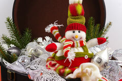 Funny snowman sits on vintage brouwn coffer with white christmas Royalty Free Stock Photo