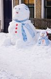 Funny Snowman and son. In front of house in the street  - vertical image Royalty Free Stock Photography