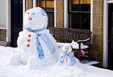 Funny Snowman and son. In front of house in the street - horizontal image Royalty Free Stock Photography