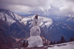 Funny snowman in spring mountains. Funny snowman on the blurry background of snowy mountains and clouds in cold tones royalty free stock photography