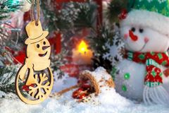 Funny snowmen with Christmas presents on the background of a red lantern and New Year`s decorations stock photography