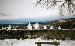 Funny snowmen created by children, a gallery of diversity. Gourdon, outdoor winter landscape, France, Maritime Alps Royalty Free Stock Photo
