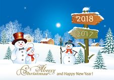 Happy New Year 2018. Funny snowmen near a wooden signpost with dates 2018 and 2017.Winter landscape Royalty Free Stock Image
