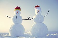Funny snowmen. Snowman couple outdoor. Christmas or xmas decoration. New year snowmen from snow in santa hat. Happy holiday and celebration. Santa claus hat in stock photography