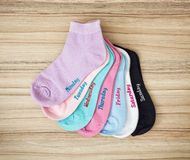 Funny socks with inscriptions of the days on the wooden backgrou Stock Photography