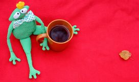 Funny soft toy prince frog with cup of tea on red carpet and fallen leaves waiting for love and princess. Royalty Free Stock Images