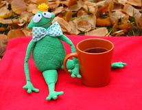 Funny soft toy prince frog with cup of tea on red carpet and fallen leaves waiting for love and princess. Waiting and dating concept. Autumn love gift and stock image