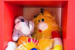 Funny soft toys are sitting in a red cube. Bright, funny soft toys are sitting in a red cube. On the shelf in the children`s room Royalty Free Stock Photos