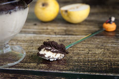 Funny spoon and creamy pear cheesecake with oreo cookies topping Stock Image