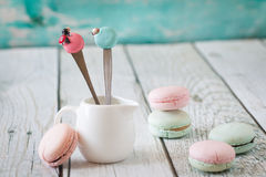 Funny spoons with macarons and ladybugs Royalty Free Stock Photo