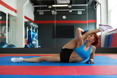 Funny sportswoman stretches at camera in gym Royalty Free Stock Image