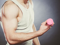Funny sporty fit man lifting light dumbbell. Fun. Stock Photos