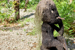 Funny statue of a man smoking made from coconut or other tree fiber, with hair of Spanish moss. Object found in a forest, with tro Stock Photography