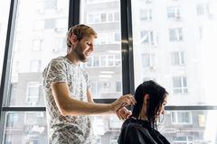 Funny story. Delighted cheerful woman laughing while hairdresser telling a funny story to her royalty free stock photo