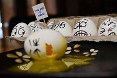 Funny egg broken on plate with other worried eggs looking on royalty free stock photos
