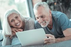 Satisfied lovely couple laughing and using the tablet. royalty free stock photography