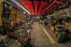 Funny street restaurant covered with red umbrellas Stock Images