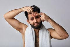 Funny strong man trying to get rid of the pimples stock photo