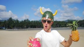 Funny strong vegan viking warrior catching tropical fruits on beach. hd slow motion. koh phangan, thailand. Funny strong vegan viking warrior catching tropical stock footage