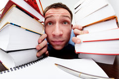 Funny student looking from behind the books. Funny student looking at camera from behind the books royalty free stock images