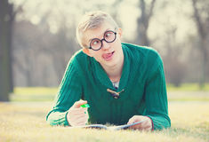 Funny student. With pen on a grass Stock Images