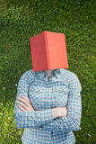 Funny Student with a Textbook. Funny top view portrait of a young student with a textbook over her head, lying on a green grass field Stock Photo