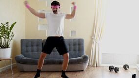 Funny stupid-looking fitness man dancing enjoying music and warming up on workout in the living room.