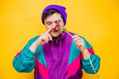 Funny style white man in 90s jacket and hat with peony flower. On yellow background stock photos