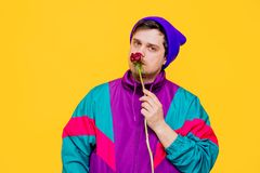 Funny style white man in 90s jacket and hat with peony flower. On yellow background stock photo