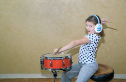 Funny styled little girl in motion practice on snare drum in studio room against vintage wall background Stock Photo