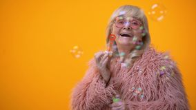 Funny stylish granny in pink coat and round sunglasses making soap bubbles, ad