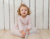 Funny stylish little girl sitting on the floor Royalty Free Stock Images
