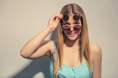 Funny summer girl. Attractive girl in summer clothes and in two pairs of sun glasses is looking at camera and smiling, against gray background Royalty Free Stock Image