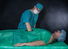 Funny surgery operation on a black background. Stock Photography