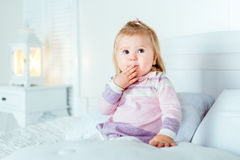 Funny surprised blond little girl sitting on bed in bedroom Royalty Free Stock Photography