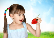 Funny surprised child girl with strawberry Stock Photo