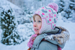 Funny surprised child girl in winter garden with falling snow Royalty Free Stock Photography