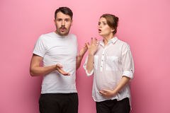 The funny surprised handsome man and his beautiful pregnant wife`s tummy Stock Photography