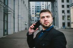 Funny surprised man and businessman talking on the phone on the background of a modern urban landscape. Business concept Stock Photos