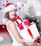 Funny surprised woman in santa hat with gifts near Christmas tre Stock Photos