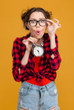 Funny surprised young woman in glasses holding alarm clock Stock Photography